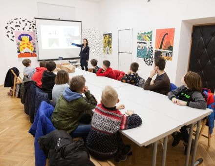 Warsztat architektoniczny [warsztat dla dzieci w ramach Zimowej Majsterni. Na zdjęciu widzimy dzieci siedzące przy stole, słuchające Pani prowadzącej. Tłumaczy ona zagadnienia związane z tematem architektury, pokazując na obraz wyświetlony przez projektor]