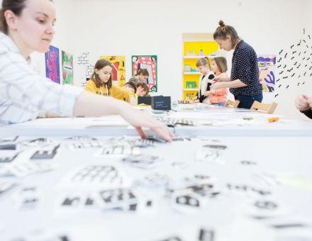 Archiplakat  [warsztat dla dzieci w ramach Zimowej Majsterni, na zdjęciu dzieci siedzące przy stole, na którym znajduje się mnóstwo kartek]
