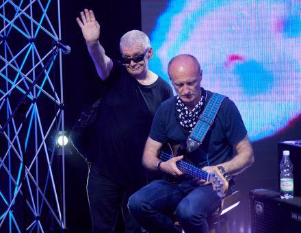 Wokalista stoi i ma podniesioną do góry rękę, macha – pozdrawia. Obok na stołku siedzi gitarzysta, jest skupiony na instrumencie. Za plecami obu mężczyzn ekran led z abstrakcyjną animacją w kolorze błękitnym.
