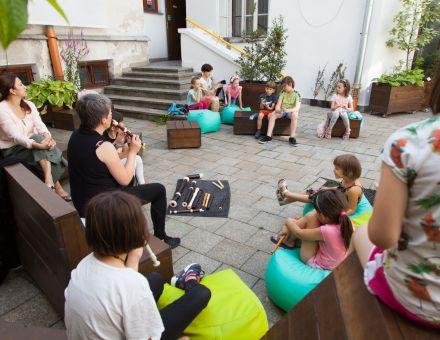 Patio Warsztatów Kultury, w kole na drewnianych ławkach siedzą uczestnicy warsztatów, dzieci i dorośli, wszyscy mają w rękach flety, niektórzy próbują grać.