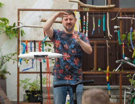 Prowadzący warsztaty pokazuje coś dłońmi. Obok niego stoi elektroniczny instrument muzyczny. W tle kolorowe wietrzne dzwonki zawieszone na drewnianym stelażu.