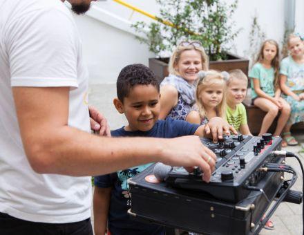 Chłopiec sprawdza jak działają suwaki i pokrętła konsolety, wszystko pod czujnym okiem prowadzącego. W tle kolejka dzieci, które także chcą spróbować.