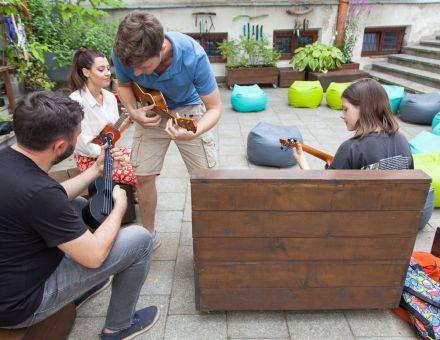 Patio Warsztatów Kultury. Na zdjęciu trzech uczestników w tym mężczyzna, kobieta i nastolatka. Wszyscy siedzą na drewnianych ławkach i trzymają w rękach ukulele. Do mężczyzny podchodzi prowadzący warsztaty, pochyla się nad nim i pokazuje mu jak trzymać chwyt na ukulele.