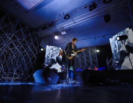 Szeroki plan, sala koncertowa, na suficie szyny z reflektorami, w tle aluminiowe kratownice, ekrany led z abstrakcyjnymi animacjami. Oświetlenie niebieskie. Na środku stoi muzyk, gra na gitarze do której na sznurkach przyczepione są pluszowe maskotki.