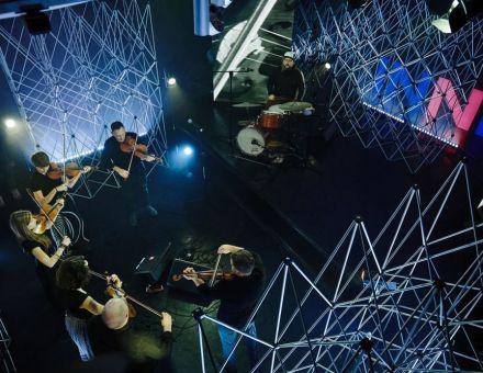 Rzut z góry.  W dole 7 instrumentalistów w studio Strefy Innych Brzmień. W  tle ledon z napisem INNE i aluminiowe kratownice.