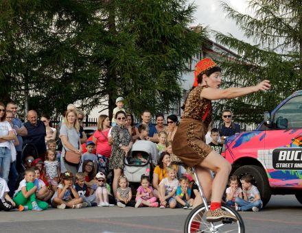 fot. Anna Kamińska [plenerowy pokaz sztuki cyrkowej, na pierwszym planie artysta jadący na monocyklu,  w tle zgromadzona publiczność]