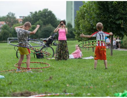 [Na zdjęciu widzimy dwóch chłopców wykonujących ćwiczenia na świeżym powietrzu przy użyciu  hula hop.  Obok rodzina leży na trawie, kobieta robi zdjęcia chłopcom]