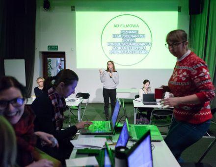 Inkubator Kultury | Audiodeskrypcja  [ szkolenie z audiodeskrypcji. Na zdjęciu uczestnicy projektu Inkubator Kultury, pracują na komputerach. W tle wyświetlony jest slajd ( Ad filmowa). Prowadząca przekazuje informacje na temat audiodeskrypcji]
