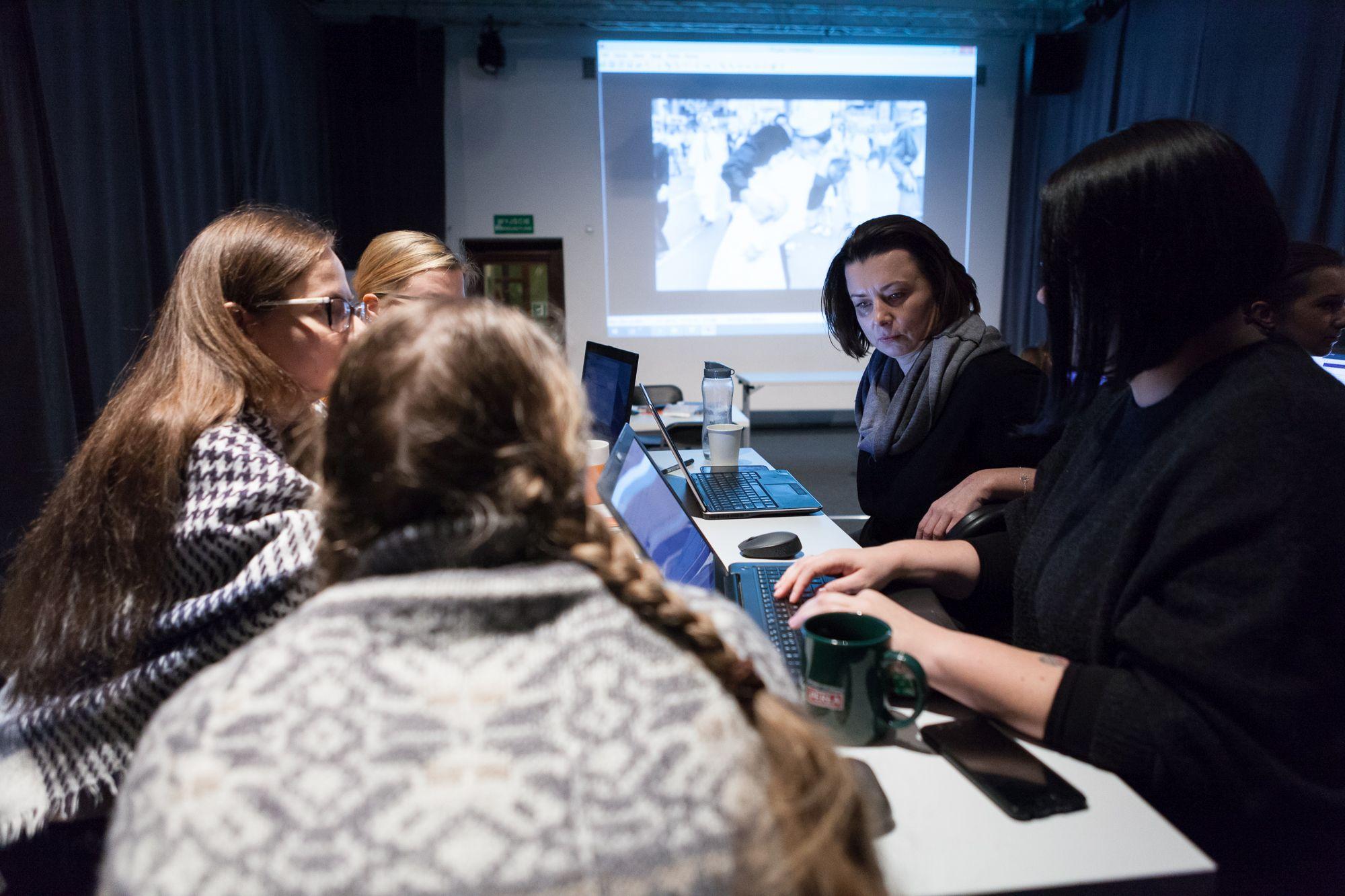 Inkubator Kultury | Audiodeskrypcja  [Szkolenie z audiodeskrypcji. Na zdjęciu uczestnicy  pracują na komputerach.  W tle wyświetlony jest slajd]