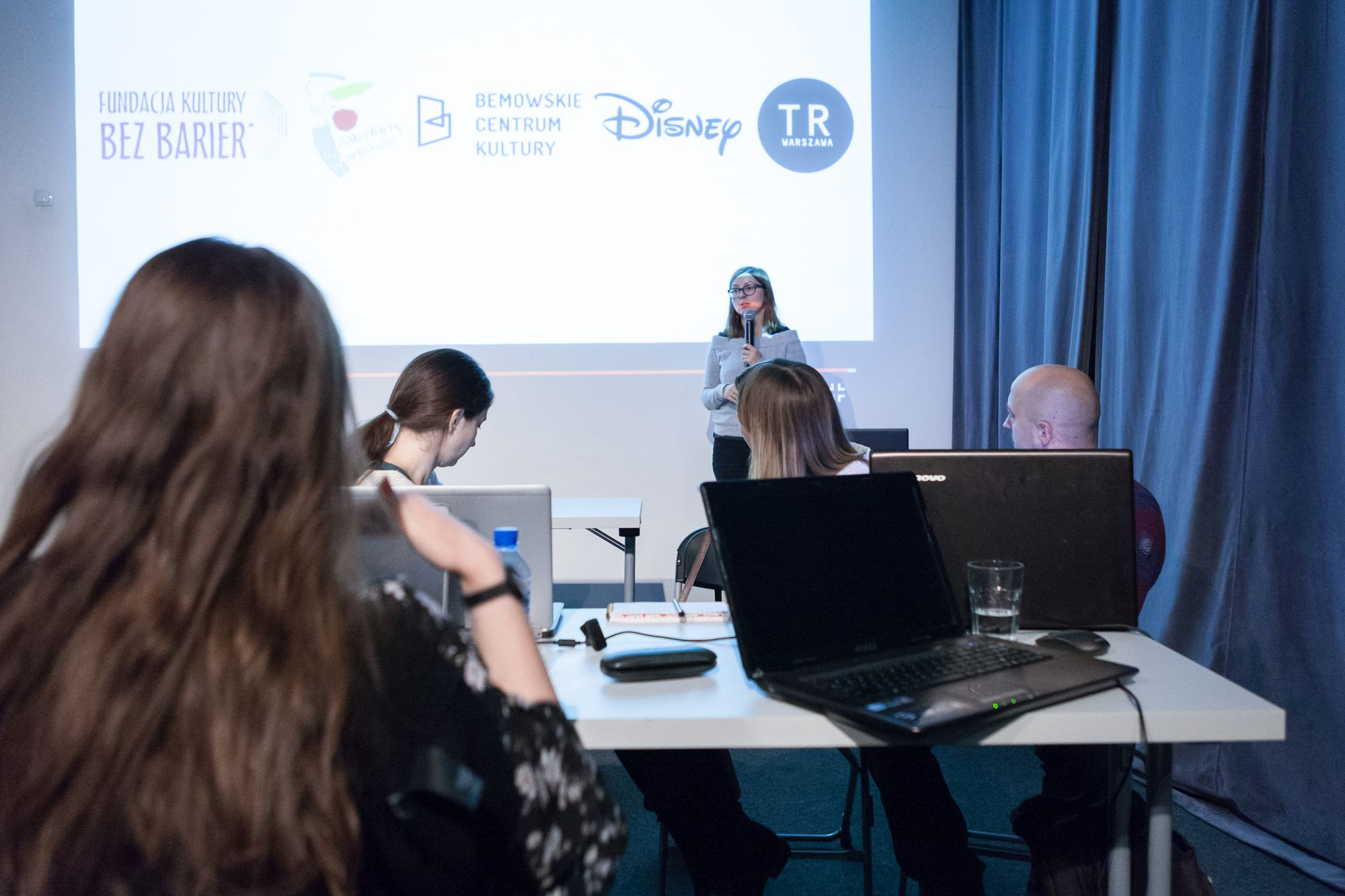 Inkubator Kultury | Audiodeskrypcja  [Na zdjęciu widać uczestników projektu przy komputerach, którzy oglądają kolejne slajdy.  Prowadząca omawia wyświetlane treści.  Na slajdzie znajdują się napisy razem z logo, tj. Fundacja kultury bez barier, Zakochaj się  w Warszawie, Bemowskie Centrum Kultury, Disney, TR Warszawa ]