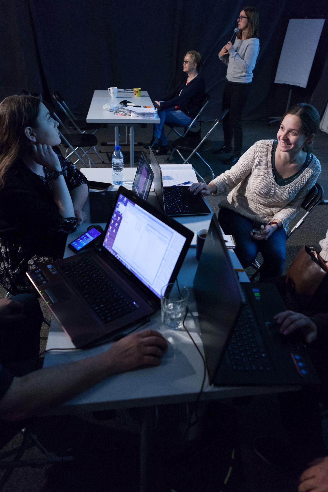 Inkubator Kultury | Audiodeskrypcja  [Szkolenie z audiodeskrypcji,. Zdjęcie ukazuje uczestników podczas pracy grupowej, w tle obie prowadzące]