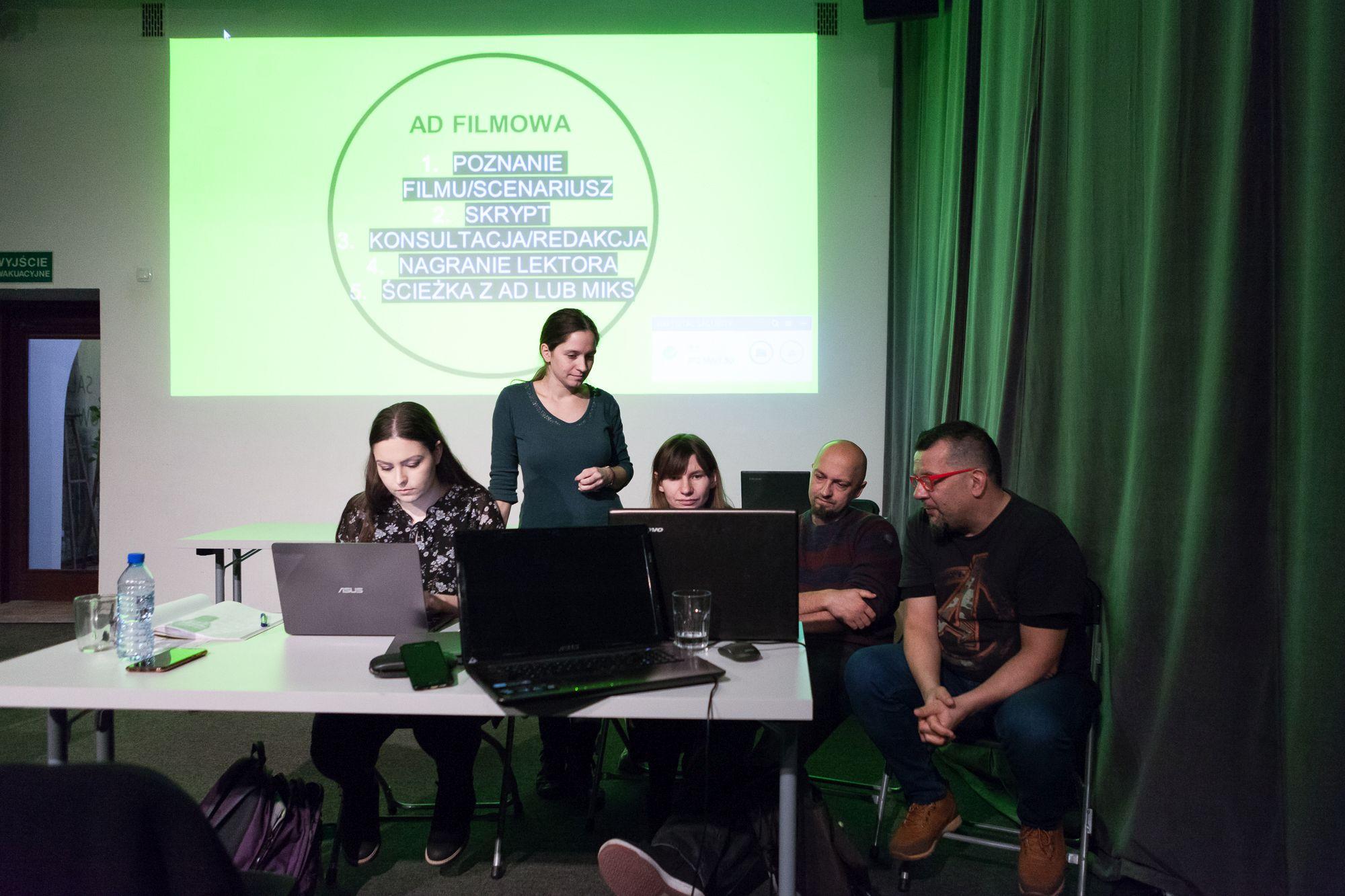 Inkubator Kultury | Audiodeskrypcja  [Na zdjęciu uczestnicy pracują w grupach, siedząc przed komputerami, za nimi wyświetlony jest slajd ( Ad filmowa). ]