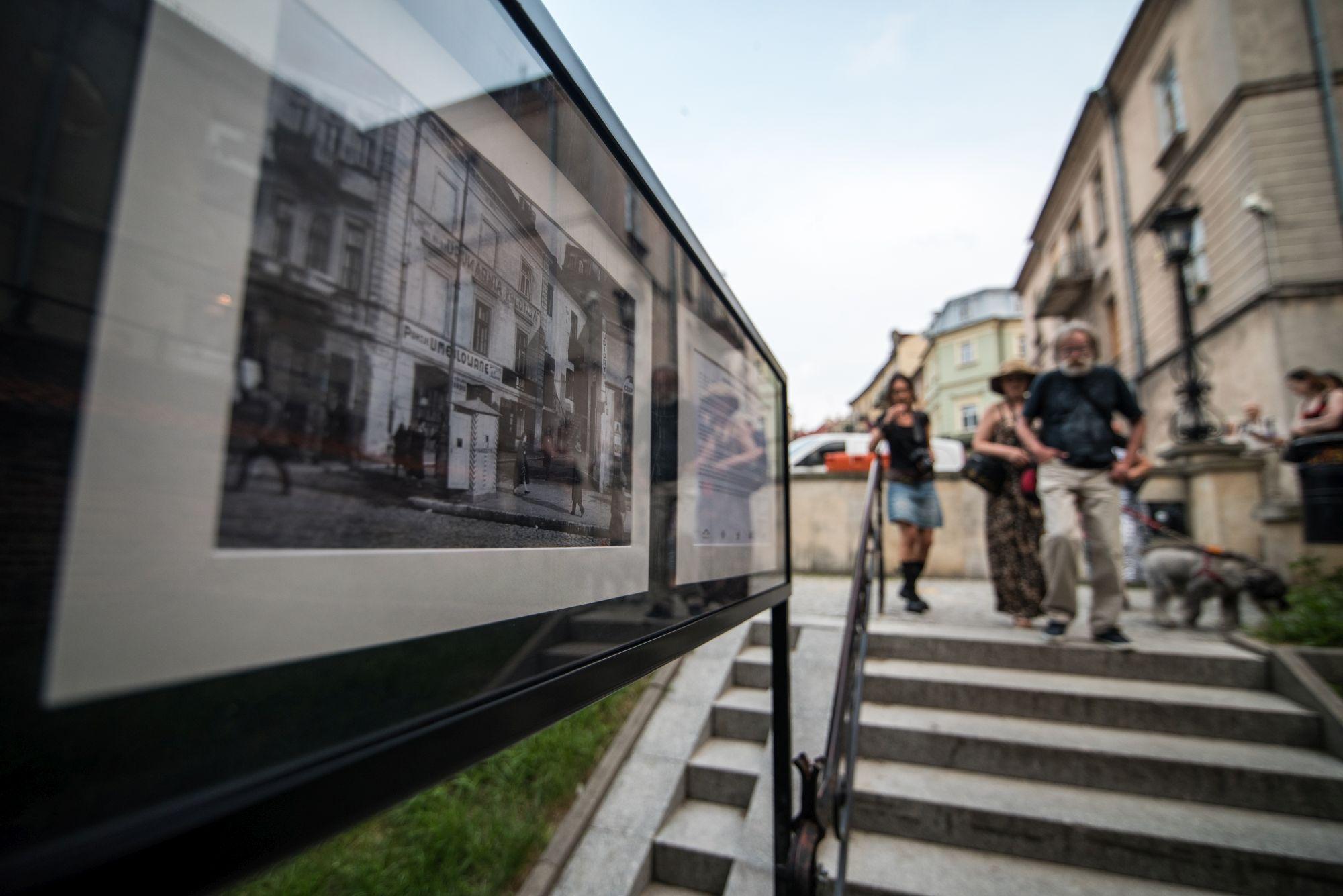 Kiełsznia - dokumentalista Lublina [galeria fotografii w Zaułku Hartwigów, zbliżenie na fotografię, w tle odwiedzający]