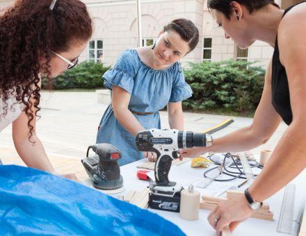 Warsztat stolarski – drewniana lampa  [Plenerowy warsztat w ramach lekcji sztuki. Plac Litewski, trzy kobiety, uczestniczące w wydarzeniu. Konsultują się, wykonując przy tym prace w drewnie]
