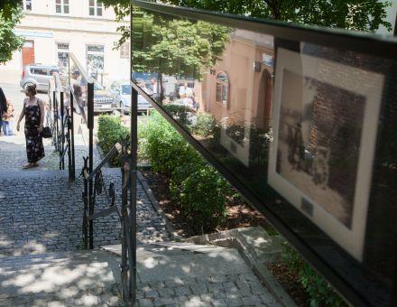 Ludzie Podola Michała Greima  [plenerowa wystawa w Zaułku Hartwigów, na zdjęciu widać spacerujących wzdłuż wystawy ludzi]