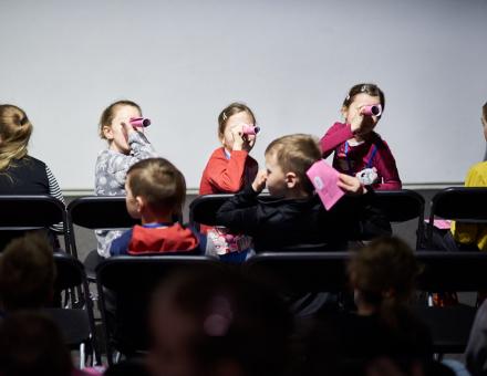 Szczęśliwa siódemka  [klub filmowy dla najmłodszych w ramach Magicznej Latarni. Na zdjęciu widzimy zgromadzone na widowni dzieci. Trzy dziewczynki z pierwszego rzędu, odwracają się do dalszych rzędów. Zrobiły lornetki z komiksów tematycznych i przyglądają się innym]