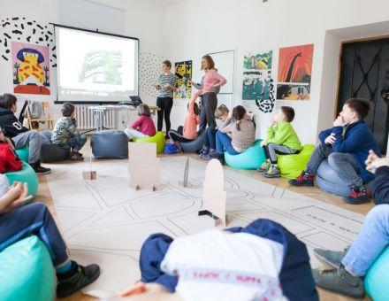 Mali architekci  [ warsztat dla dzieci w ramach Małej Majsterni. Na zdjęciu widać dzieci siedzące w okręgu i przyglądające się prezentacji. Dwie prowadzące opowiadają o architekturze. Na środku znajduje się wielkoformatowa tekturowa makieta miasta]