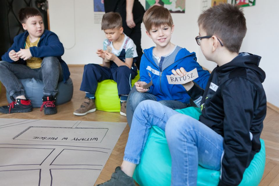 Mali architekci  [ warsztat dla dzieci w ramach Małej Majsterni. Zdjęcie ukazuje czterech chłopców, konsultujących się w parach. Trzymają w rękach karteczki. Na jednej z nich widnieje napis- ratusz]