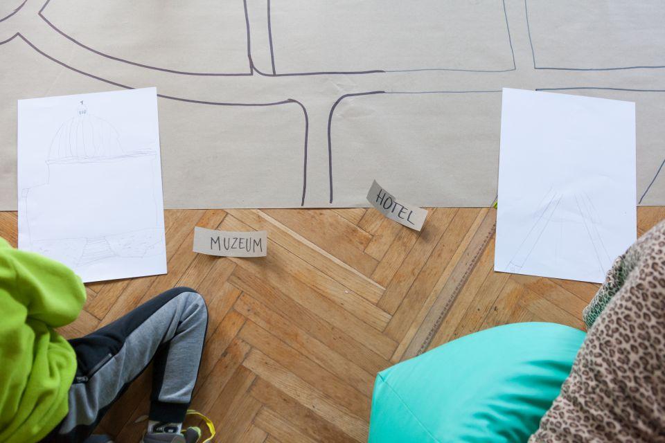 Mali architekci  [ warsztat dla dzieci w ramach Małej Majsterni. Zdjęcie robione z góry. Widać  na nim fragment makiety, dwie białe kartki z naniesionymi szkicami oraz karteczki z napisem muzeum oraz hotel. Widać zarys dzieci siedzących obok]
