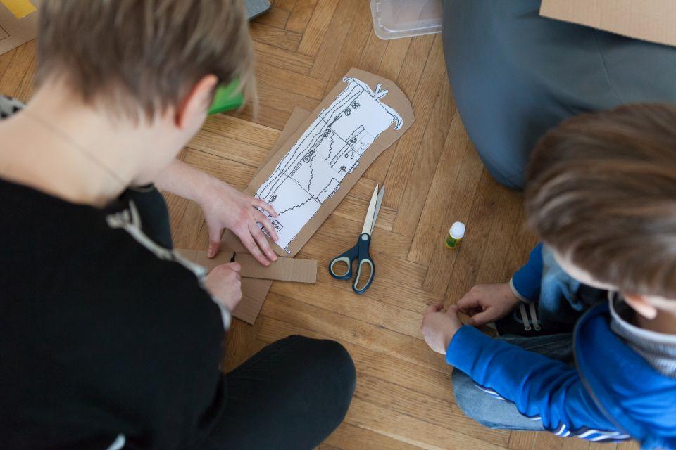 Mali architekci [ warsztat dla dzieci w ramach Małej Majsterni. Na zdjęciu dwóch chłopców rozrysowuje, tworzy budynki, które zostaną umieszczona na makiecie]