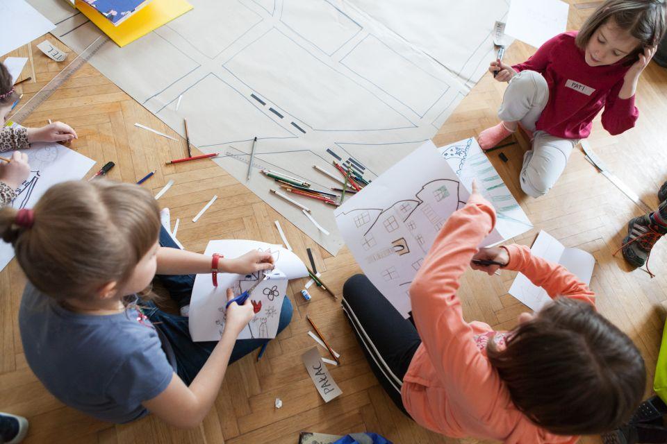 Mali architekci  [ warsztat dla dzieci w ramach Małej Majsterni. Zbliżenie na trzy dziewczynki, które wycinają i rozrysowują budynki, obiekty]
