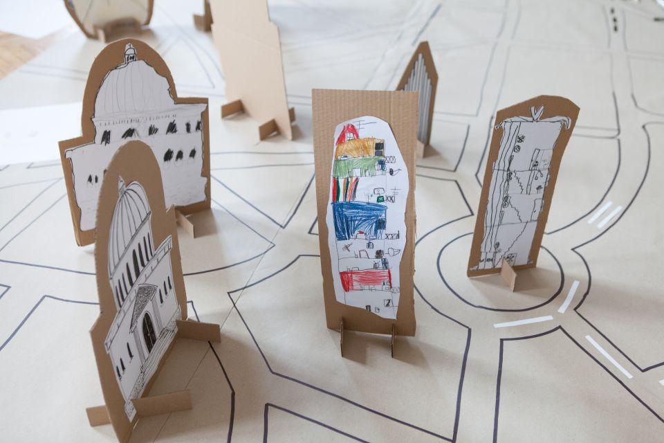 Mali architekci  [ warsztat dla dzieci w ramach Małej Majsterni. Na zdjęciu widać tekturową makietę  miasta wzbogaconą o umieszczone na niej budynki wykonane przez dzieci]