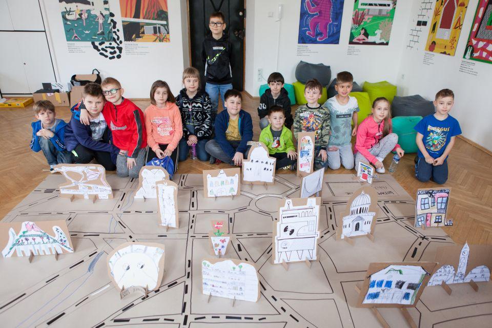 Mali architekci [ warsztat dla dzieci w ramach Małej Majsterni. Zdjęcie ukazuje wszystkich uczestników warsztatu wraz z makietą miasta]