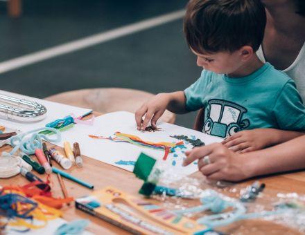 """fot. Jakub Bodys [jeden z uczestników warsztatu """"Każdy kompozytorem może być"""" - dziecko w niebieskiej koszulce siedzi na kolanach swojej opiekunki i razem tworzą pracę plastyczną na kartce papieru]"""