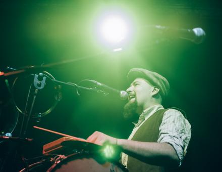 fot. Jakub Bodys [Na zdjęciu Adam Sobolewski grający na instrumentach perkusyjnych w zespole Hańba! Artysta oświetlony jest ostrym światłem reflektora.]