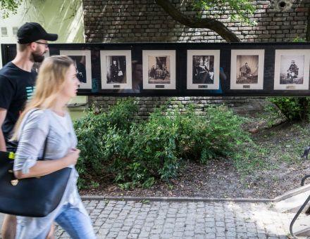 """Wojna Krymska  [przechodnie na zaułku Hartwigów, spoglądają w strone prac wystawy plenerowej galerii fotografii Warsztatów Kultury """"WOJNA KRYMSKA – WYSTAWA FOTOGRAFII ROGERA FENTONA""""]"""