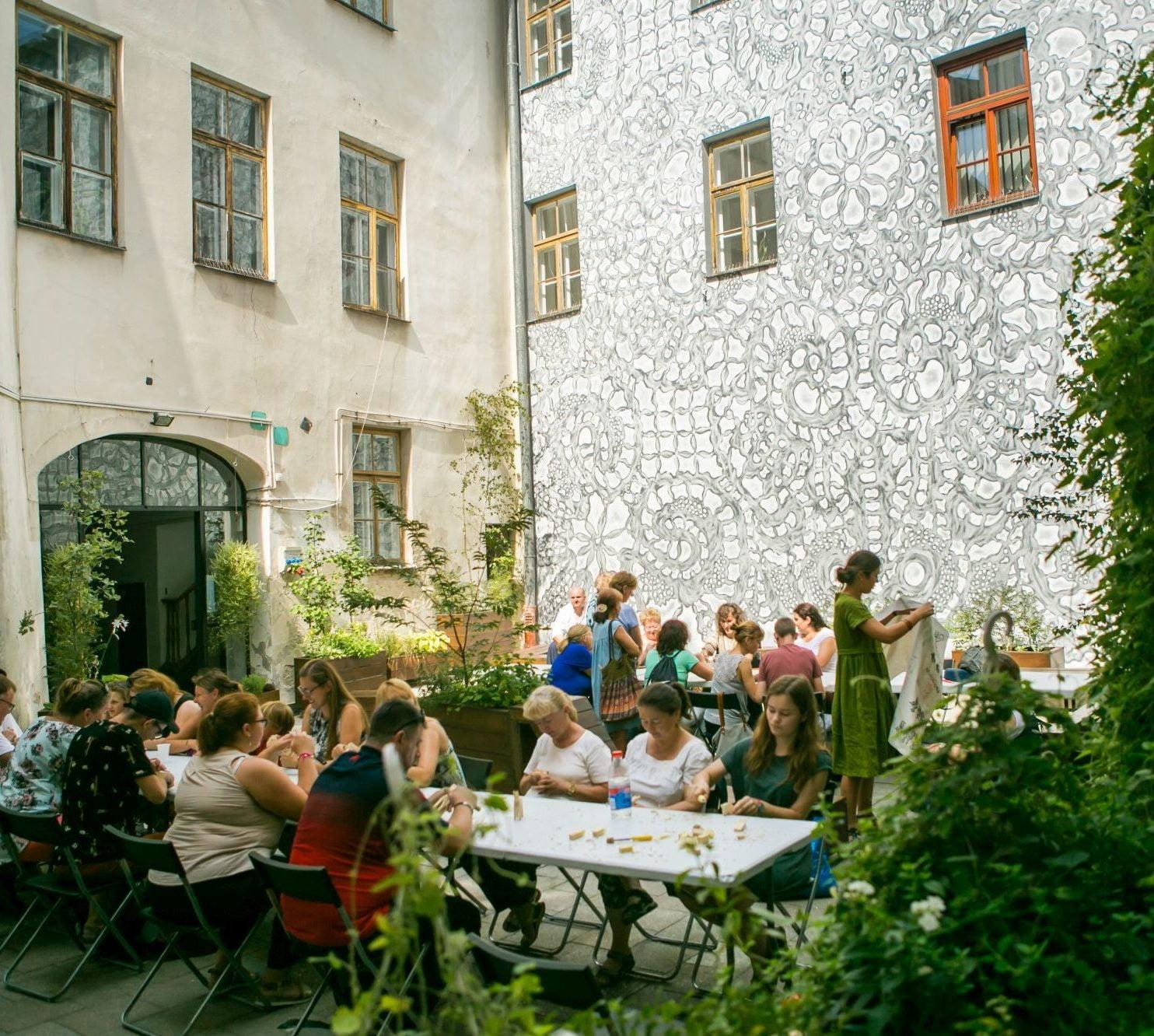 Patio kamienicy, w której siedzibę mają Warsztaty Kultury. Na patio, pośród zieleni rozstawione są stoły, przy których odbywają się warsztaty