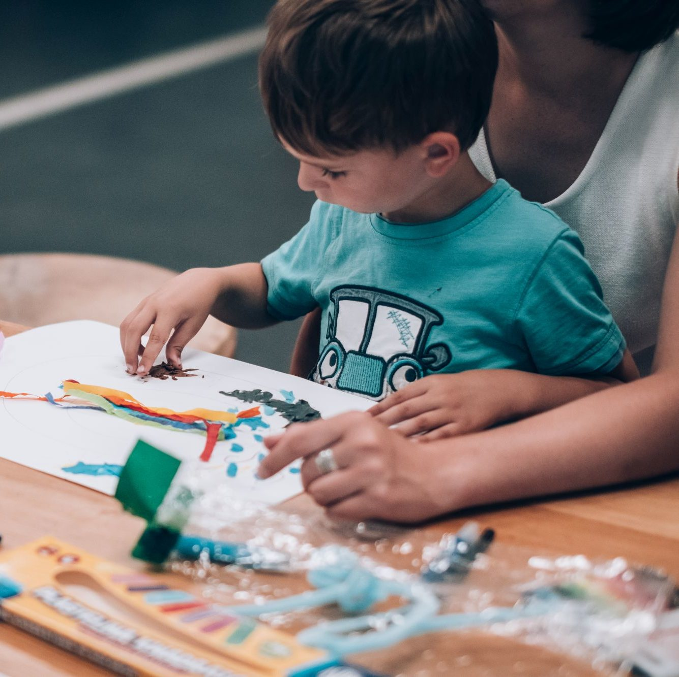 Dziecko wykleja plasteliną obrazek na kartce