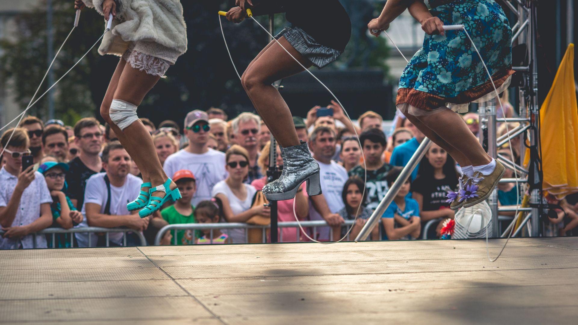 widzowie patrzą na scenę, na której trzy osoby skaczą przez skakanki. Zdjęcie uchwyciło je podczas wyskoku w górę, widoczne są jedynie fragmenty sylwetek, głowy artystów znajdują się poza kadrem
