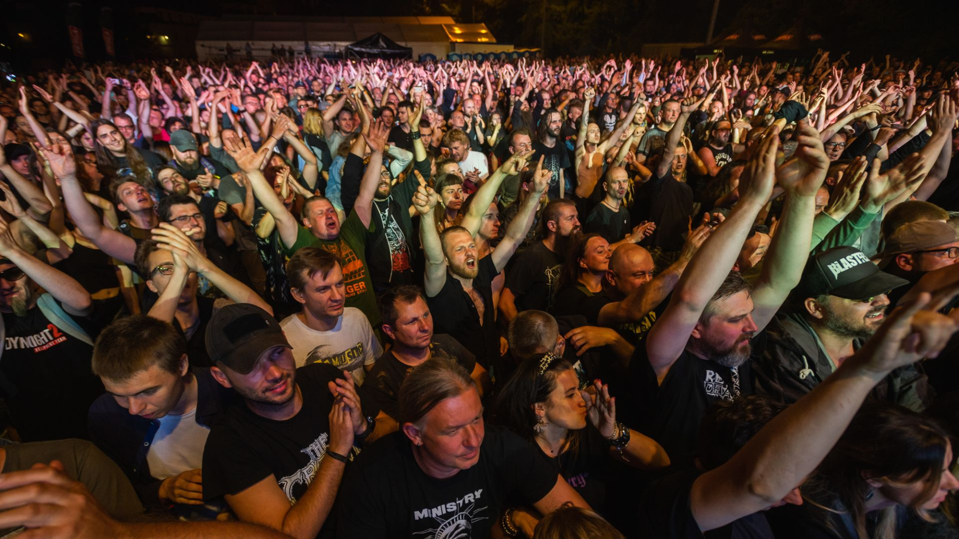 The photo shows the audiences at East of Culture - Different Sounds in front of a music stage. Na zdjęciu publiczność festiwalu Wschód Kultury - Inne Brzmienia pod sceną koncertową. The crowds are holding their arms up in the air and are screaming enthusiastically