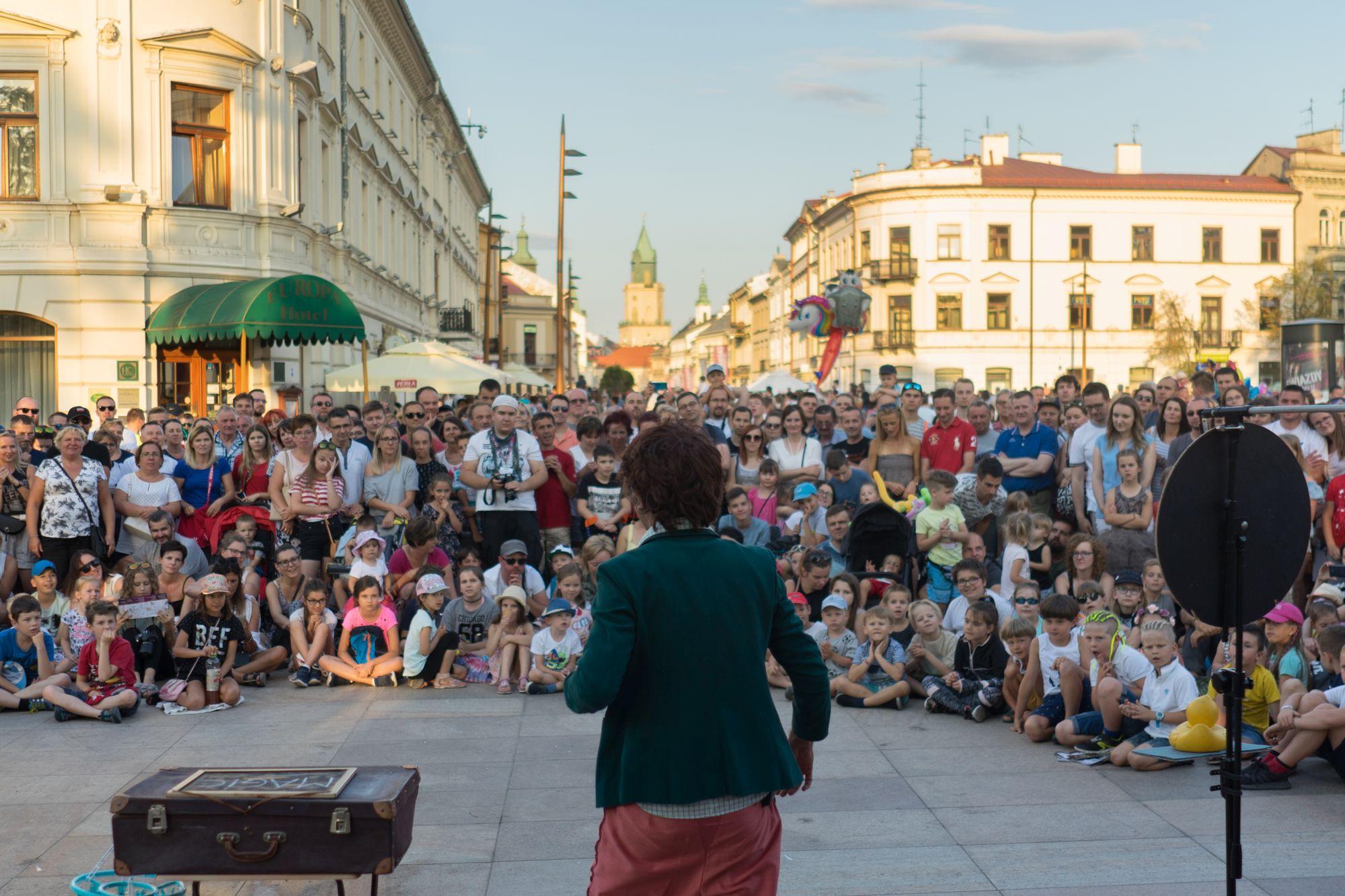 Na zdjęciu busker w trakcie pokazu na Placu Litewskim w Lublinie, przed nim czekająca na pokaz publiczność.