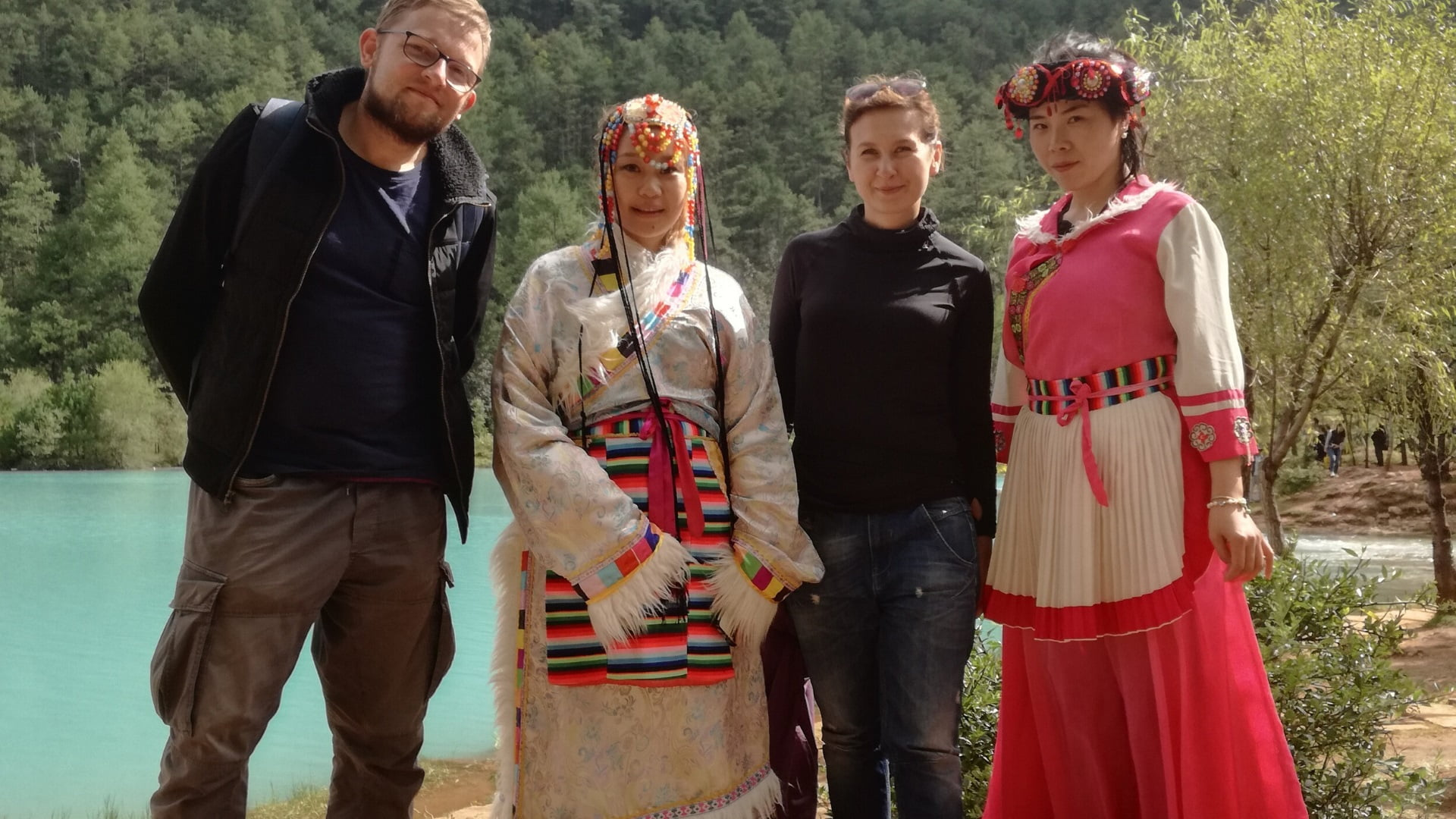 Two employees of Workshops of Culture pose during their trip to China pose with women in traditional costumes.