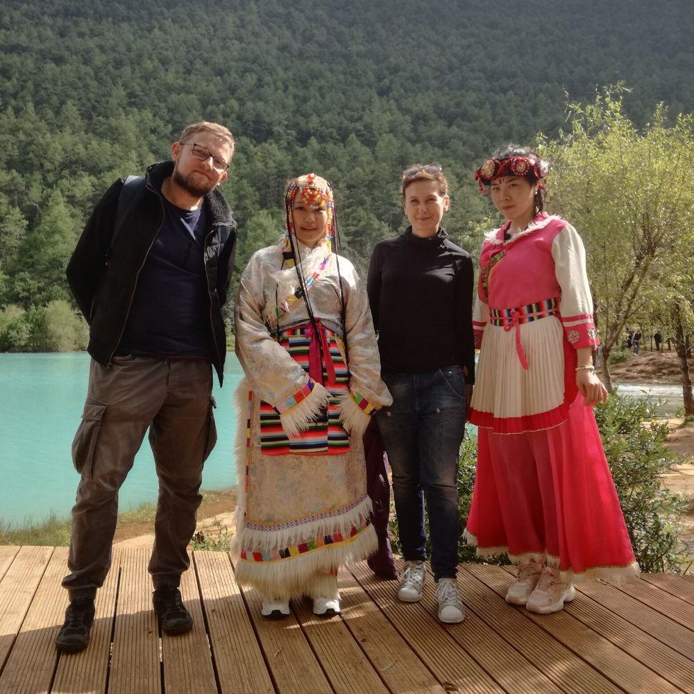 Dwoje pracowników Warsztatów Kultury podczas wyjazdu do Chin pozuje z kobietami w tradycyjnych strojach.