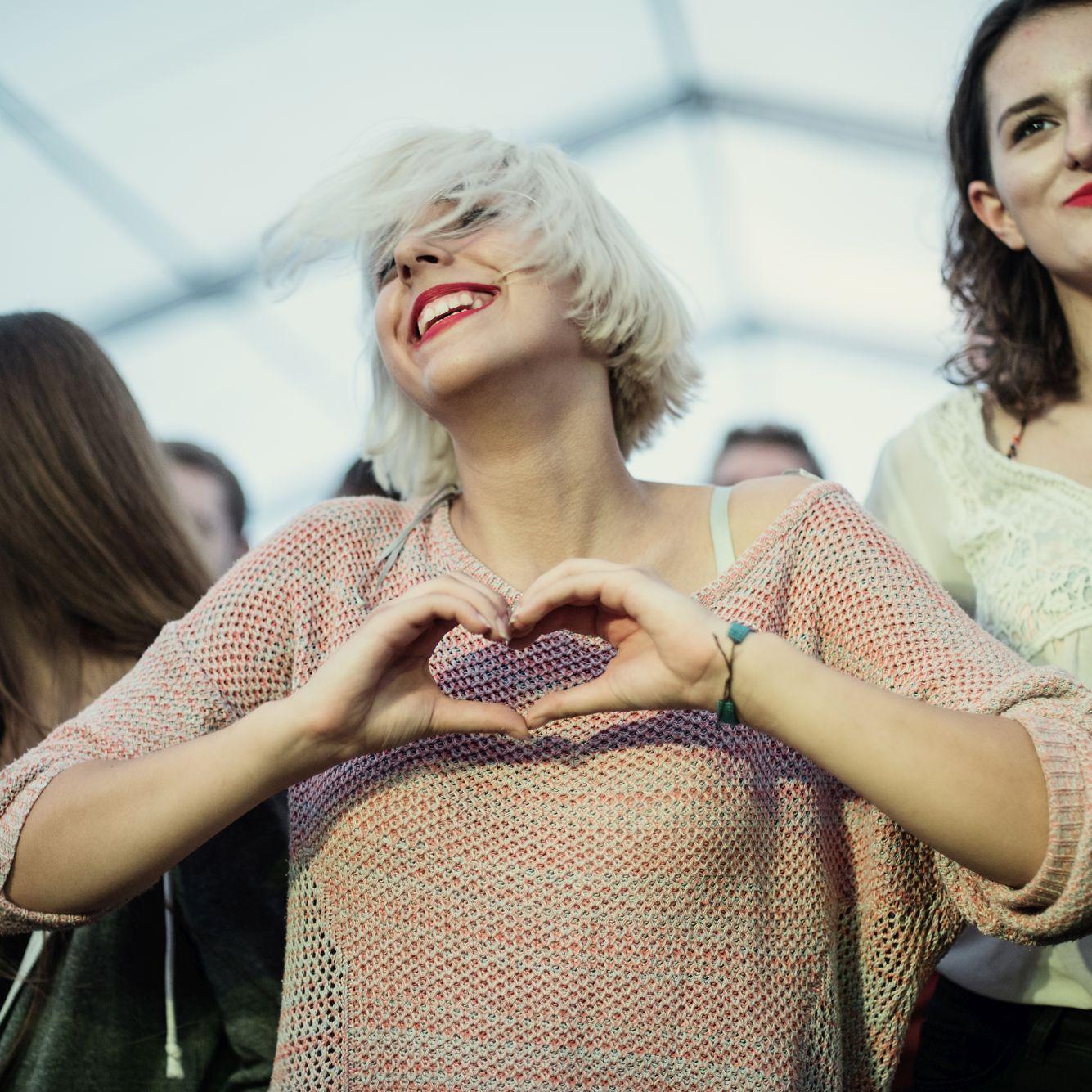 [na zdjęciu dziewczyna mająca złożone dłonie w symboliczne serce
