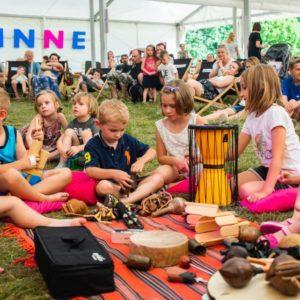 Zdjęcie z Finału Małych Innych Brzmień 2019. Na trawie pod dużym białym namiotem siedzi grupka dzieci. Przed nimi na kocu znajdują się różne instrumenty - grzechotki, bęben i drobne drewniane instrumenty. W tle na leżakach siedzą dorośli i inne dzieci