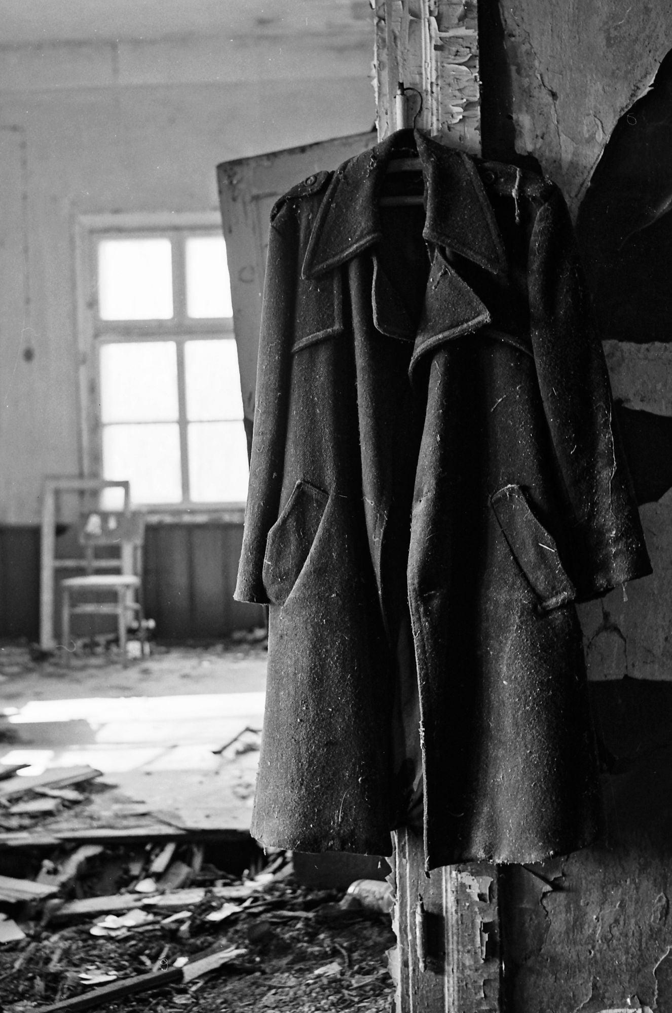 Czarno-białe zdjęcie przedstawia wnętrze opuszczonego, zdewastowanego pomieszczenia. Na pierwszym planie stary zniszczony płaszcz wiszący na haku wbitym w futrynę. Na podłodze śmieci, połamane drewno. W tle stare krzesło i duże, jasne okno.