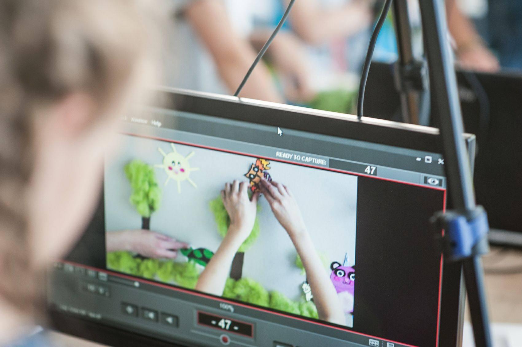zdjęcie ukazuje ekran monitora, na którym powstaje animacja poklatkowa. dłonie animują przedmioty