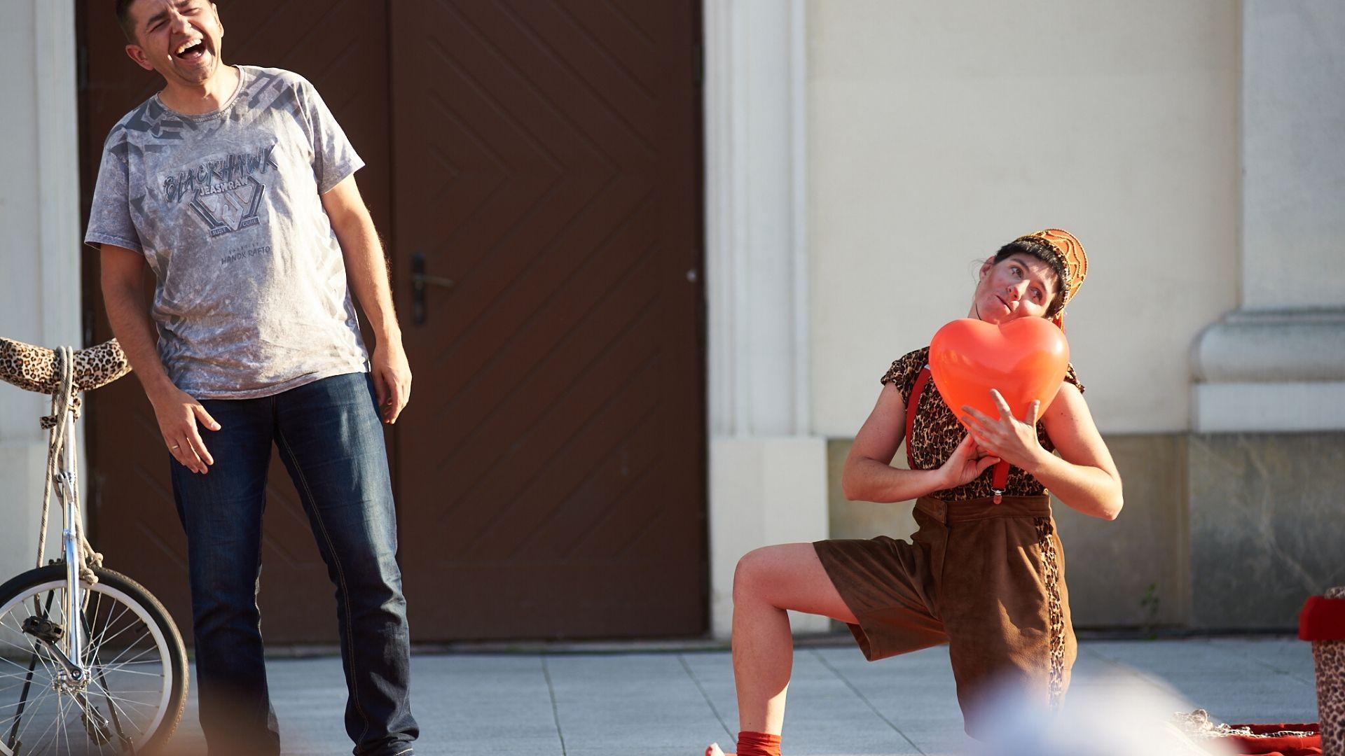 Zdjęcie z Carnavalu Sztukmistrzów 2019. Artystka ubrana w krókie spodenki na szelkach przyklęknęła na jedno kolano. W rękach trzyma czerwony balon w kształcie serca. Obok niej stoi mężczyzna, śmieje się. Przy mężczyźnie widoczny rekwizyt - monocykl