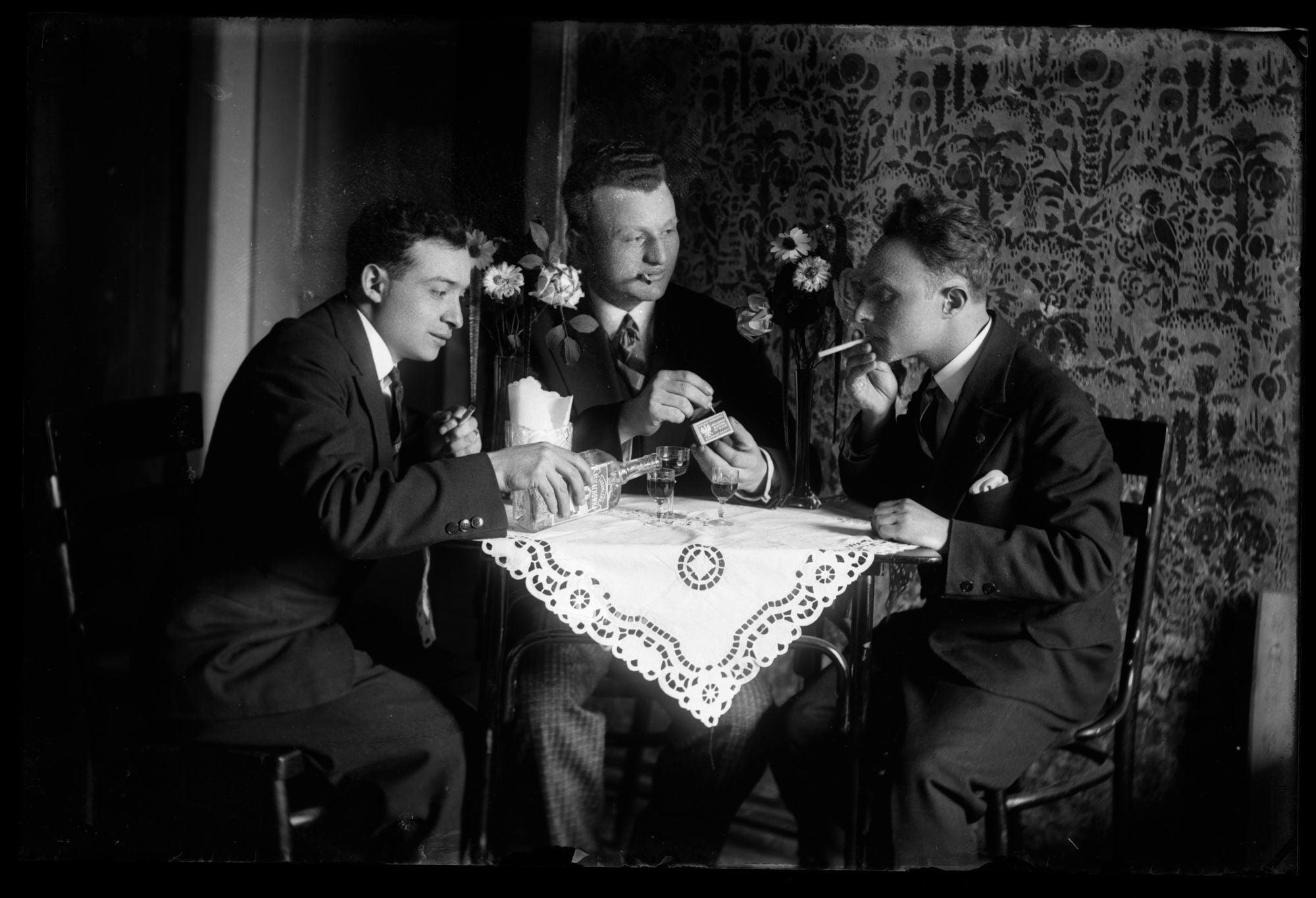 Czarno-białe zdjęcie z początków XX-tego wieku. Trzech mężczyzn przy stole piją wódkę i palą papierosy.