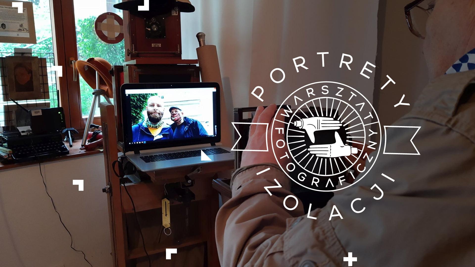 Fotografia przedstawia laptop we wnętrzu atelier fotograficznego. Na pierwszym planie widzimy fotografa, który  próbuje uwiecznić postacie wyświetlające się na ekranie laptopa, używając do tego tradycyjnego aparatu analogowego.