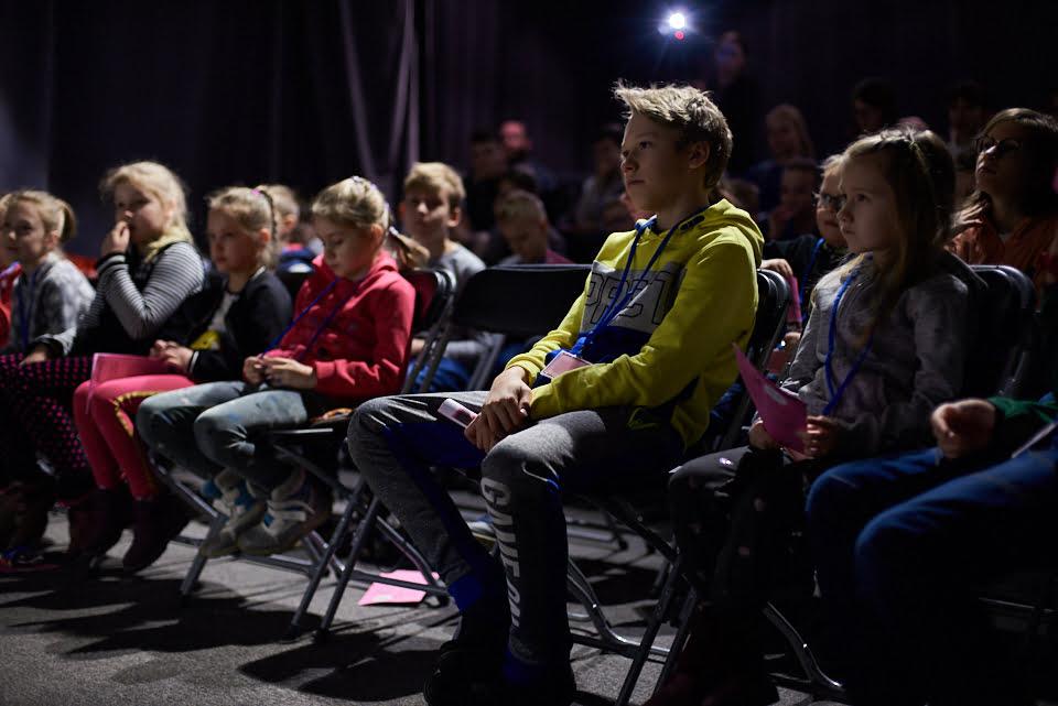 Zdjęcie z pokazu Magicznej Latarni. W sali widowiskowej Warsztató Kultury na krzesełkach siedzą dzieci oczekujące na pokaz filmu