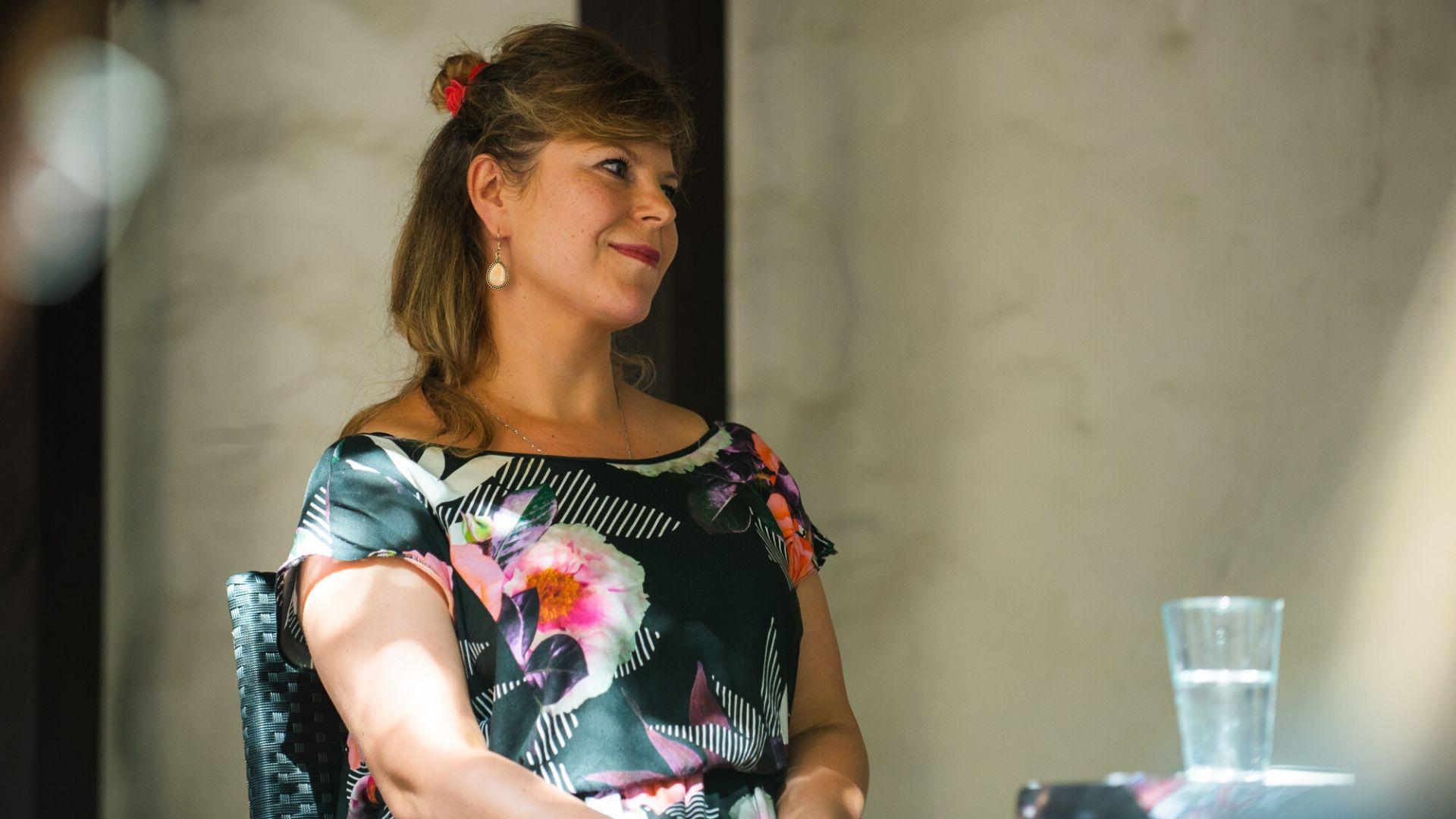 Aleksandra Zińczuk, prowadząca spotkanie literackie. Ubrana w kwiecistą sukienkę, wpatrzona w dal, poza kadr.