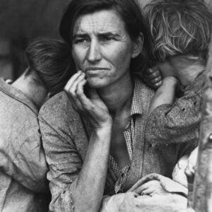 Czarno-białe zdjęcie. Na zdjęciu kobieta ze zmartwioną miną, wpatrzona w dal. Na jej ramionach oparte dzieci, zwrócone tyłem do obiektywu. Wszyscy wydają się zmęczeni i brudni.