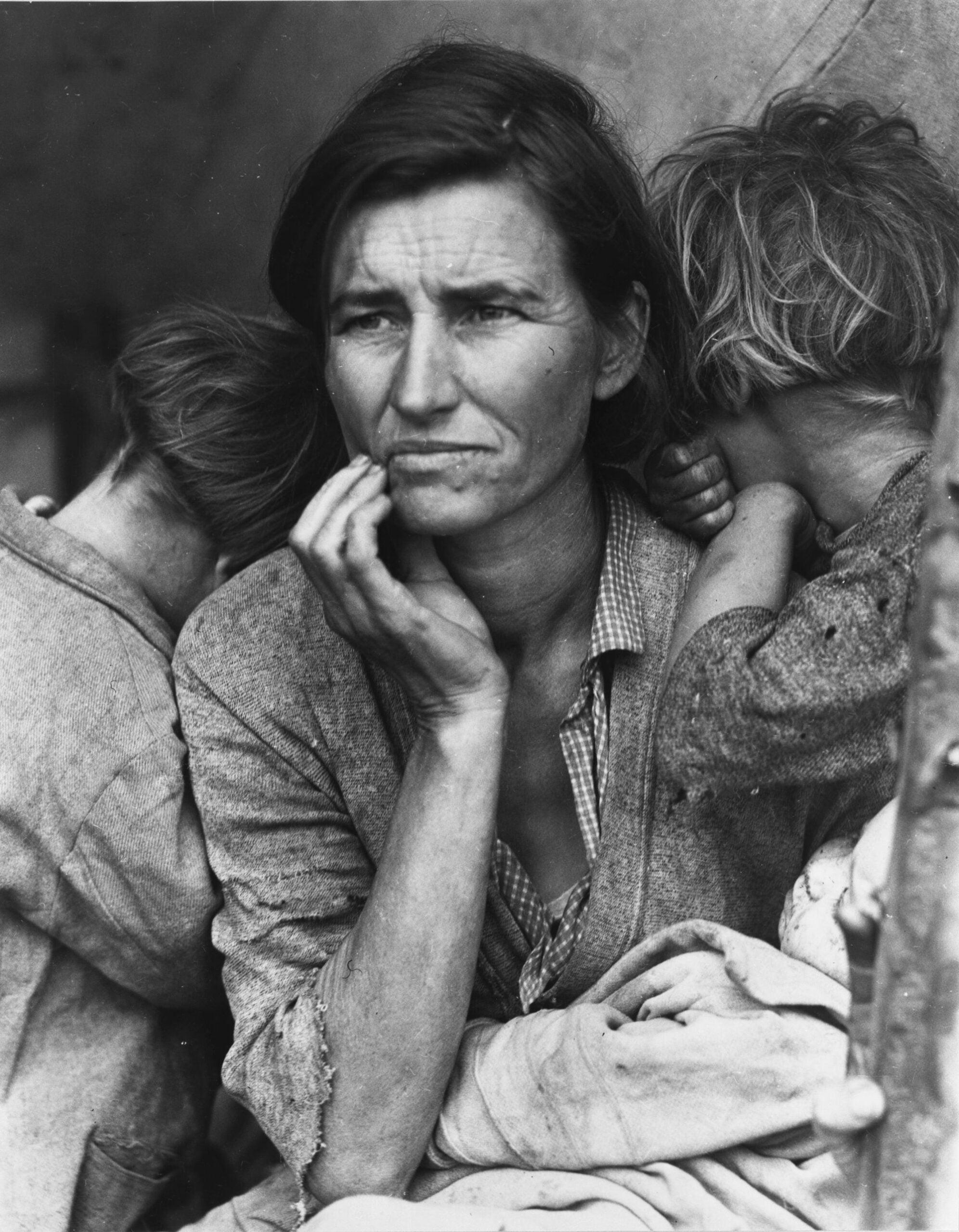 Czarno-białe zdjęcie. Na zdjęciu kobieta ze zmartwioną miną, wpatrzona  w dal. Na jej ramionach oparte dzieci, zwrócone tyłem do obiektywu. Wszyscy wydają się zmęczeni i
