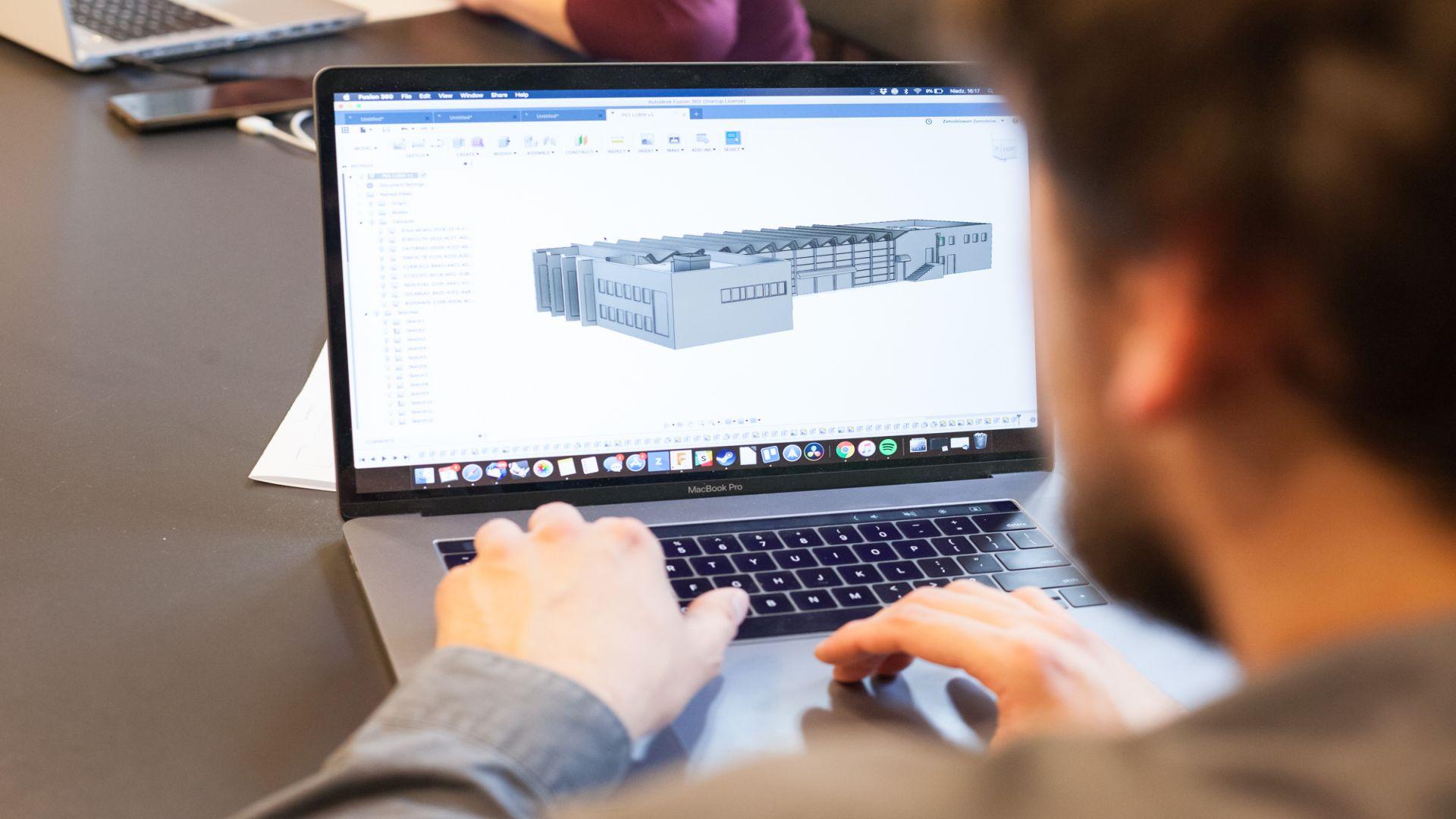 Zdjęcie ilustracyjne. Mężczyzna widziany z tyłu pracuje na laptopie, projektując budynek.