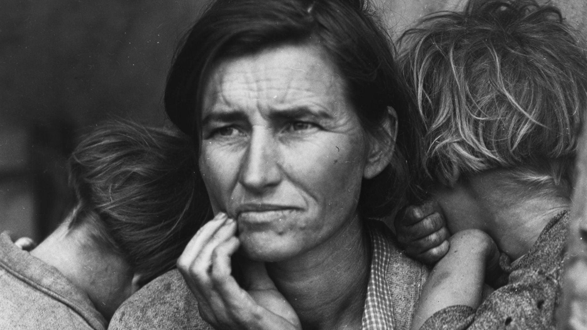 Zdjęcie czarno-białe. Na pierwszym planie twarz kobiety, ok. 40 lat, wygląda na zmęczoną, zmartwioną i zamyśloną. Ma czarne włosy założone za uszy, przedziałek po lewej stronie. Podpiera się prawą ręką pod brodą. Z dwóch stron wtulają się w nią dzieci, które są odwrócone tyłem.